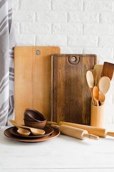Placas de cerâmica, talheres de madeira ou bambu, tábuas de corte e toalha no interior da cozinha.