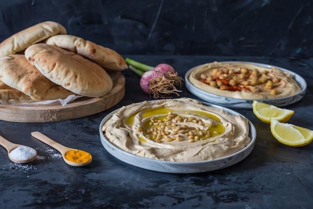 Placas de hummus com pão pita em fundo preto