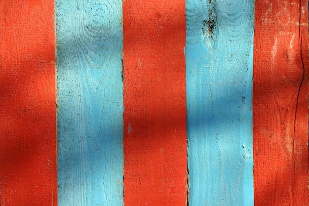 Placas de madeira da cerca pintadas em vermelho e em azul.