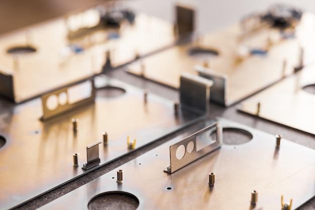 Placas de metal e acessórios ficam na superfície durante a produção de computadores modernos especializados e equipamentos médicos profissionais. conceito de produção de tecnologia