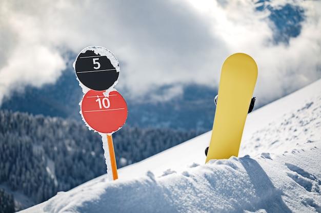 Placas numéricas de declive e snowboard em pé na borda de uma pista de esqui