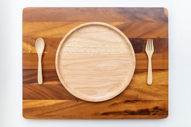 Placas redondas de madeira de borracha com cores naturais, polidas e lacadas, colocadas sobre um bloco de corte de madeira de acácia