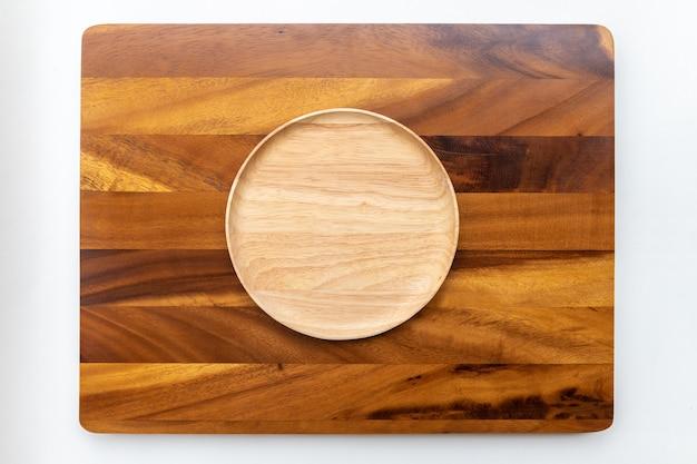 Placas redondas de madeira de borracha com cores naturais, polidas e lacadas, colocadas sobre uma tábua de madeira de chamchuri ou mimosa com fundo branco.