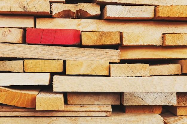 Placas serradas e dobradas com ênfase em uma placa vermelha, placas de construção, fundo de madeira serrada em tela cheia.