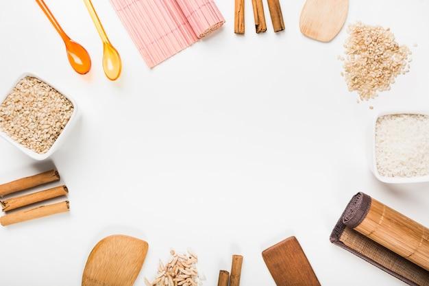 Placemat; colher; arroz cru; paus de canela; espátula em fundo branco
