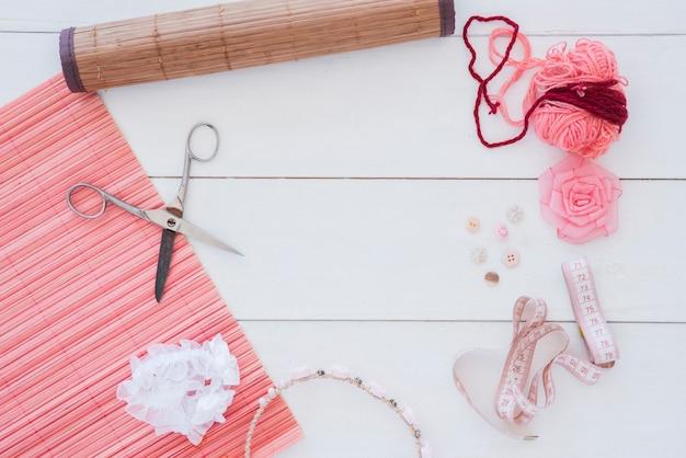 Placemat de bambu; tesoura; lã; fita rosa; elástico de cabelo; botão e fita métrica na mesa de madeira