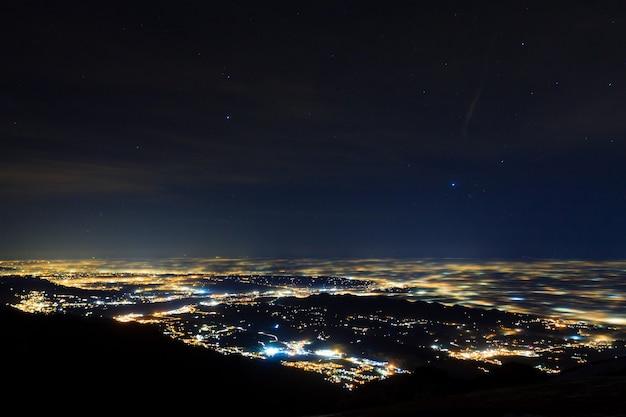 Plain iluminado parcialmente coberto por nevoeiro, luzes suaves. monte grappa, paisagem italiana