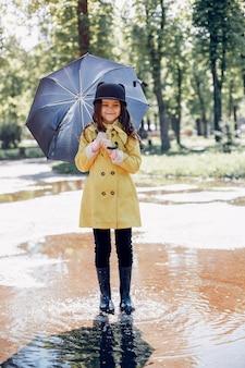 Plaiyng de criança fofa em um dia chuvoso