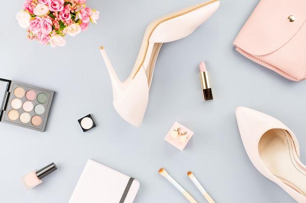 Plana leigos com bombas, cosméticos, bolsa, livro planejador e flores.