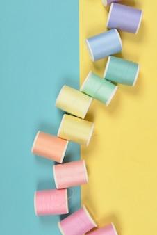 Plana leigos de rolos de linhas coloridas para costura em fundo de dois tons