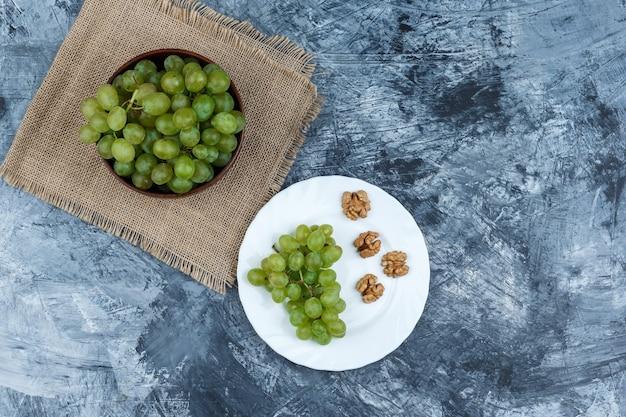 Plana uvas brancas em uma tigela com uvas, nozes em um prato branco sobre fundo de mármore azul escuro. horizontal