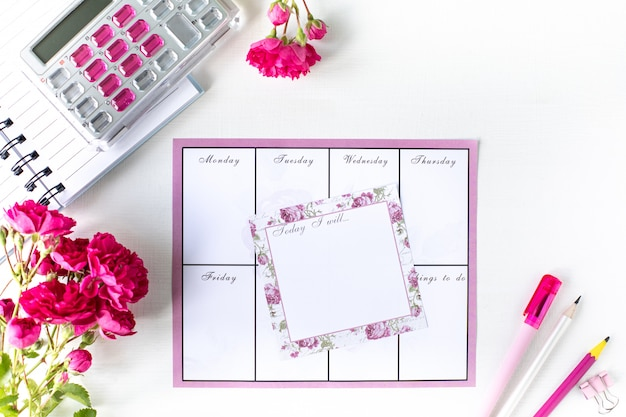 Planador com notas e lista de tarefas em um fundo branco com artigos de papelaria rosa. conceito de negócios