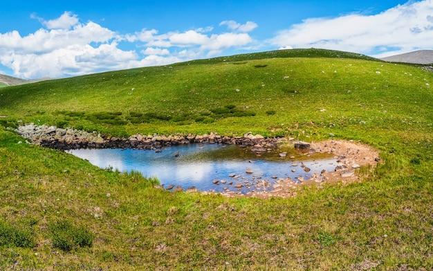Planalto pantanoso verde e uma poça azul contra o fundo de montanhas montanhosas distantes. um panorama de uma paisagem de puro verde.