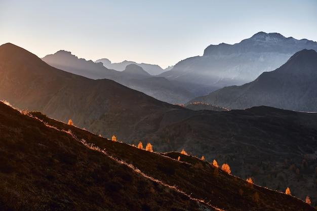 Planaltos de montanhas bonitas e picos com luz solar iluminando durante o pôr do sol