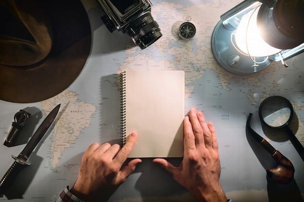 Planeamento de aventura plana leigos perto da lâmpada de gás com mãos de viajante ou alpinista na moldura, escrevendo no bloco de notas