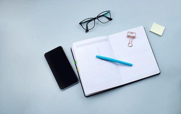 Planejador aberto, smartphone e óculos na superfície cinza claro conceito de trabalho de impostos para pequenas empresas