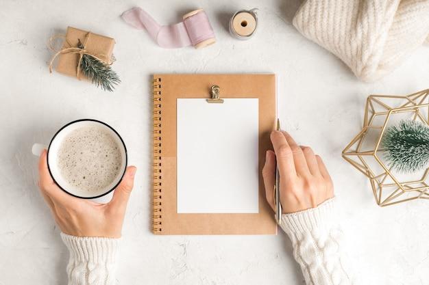 Planejador de área de trabalho em branco. camada plana do fundo branco da mesa de trabalho com uma xícara de café e decoração de natal