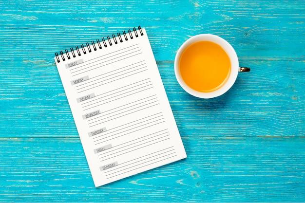 Planejador de semana vazio na mesa turquesa, conceito de local de trabalho