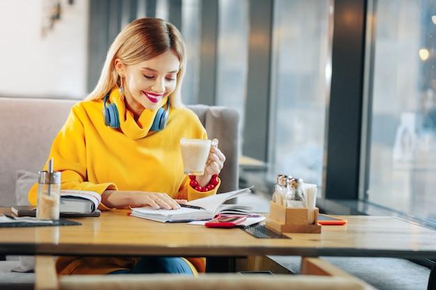 Planejador diário. mulher loira olhando para sua agenda, sentada na lanchonete