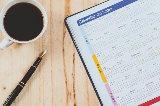Planejador do calendário com pena de fonte e café quente na tabela de madeira ferramenta de escritório.