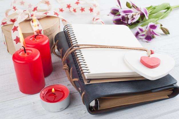 Planejador em branco aberto, com velas acesas e coração vermelho