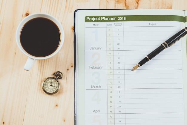 Planejador pessoal do projeto com pena de fonte e café quente na tabela de madeira.