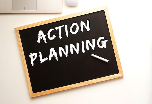 Planejamento de ação de texto escrito a giz em uma lousa. mesa de trabalho. conceito de negócios.
