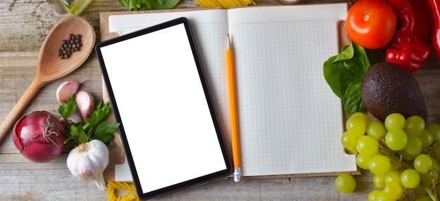 Planejamento de dieta. conjunto de alimentos crus com tablet em fundo de madeira com tela de gadget