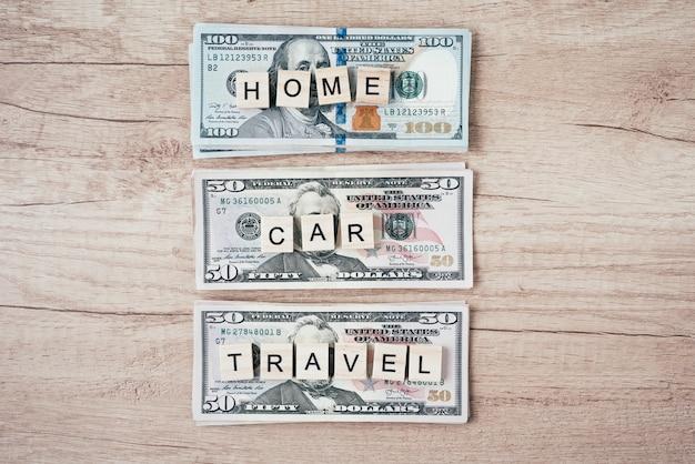 Planejamento de orçamento e conceito de riqueza. palavras carro, casa e viajar em uma notas de dólar, vista superior