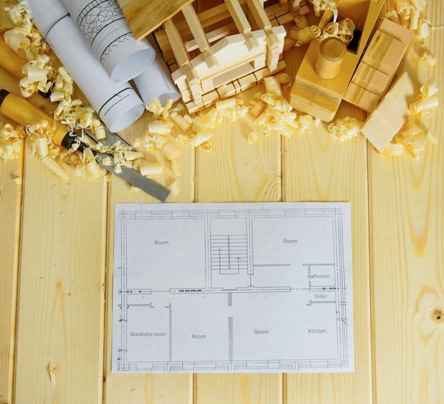 Planejamento de reparo da casa. carpintaria. desenhos de construção, pequena casa de madeira e ferramentas de trabalho sobre fundo de madeira.