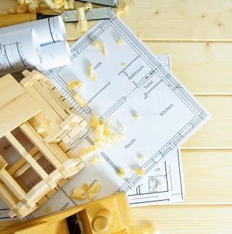 Planejamento de reparo da casa. obras de marceneiro. desenhos de construção, pequena casa de madeira e ferramentas de trabalho sobre fundo de madeira.