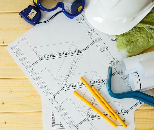 Planejamento de reparo da casa. trabalho de reparação. desenhos de construção, capacete, montagem e outras ferramentas em fundo de madeira.