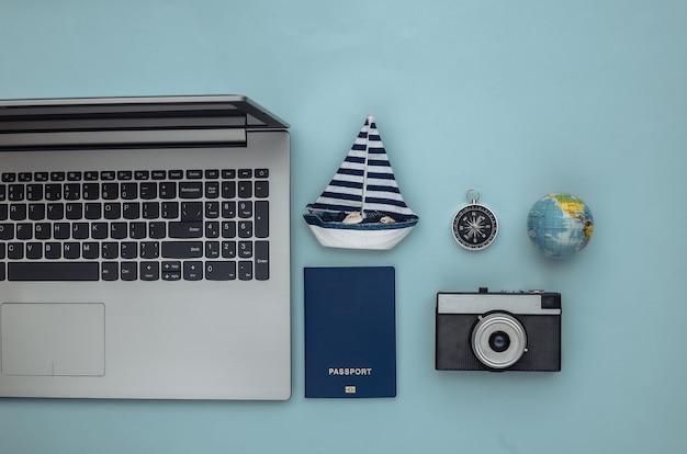 Planejamento de viagens. laptop e acessórios de viagem sobre fundo azul. vista do topo. postura plana