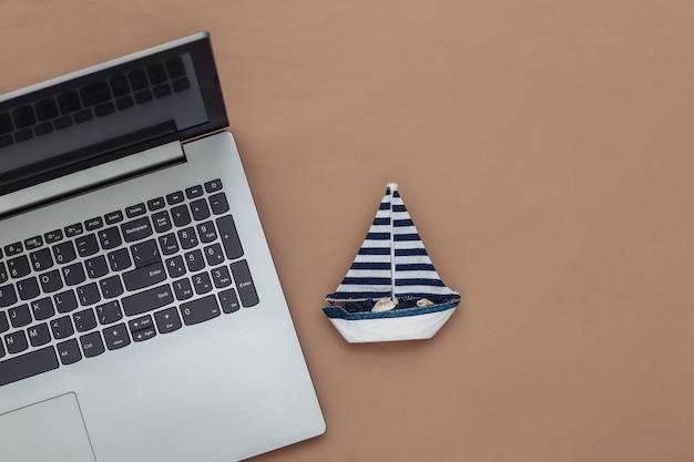 Planejamento de viagens. laptop e veleiro em um fundo marrom. vista do topo. postura plana