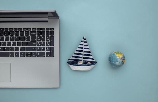 Planejamento de viagens. laptop e veleiro, globo sobre fundo azul. vista do topo. postura plana