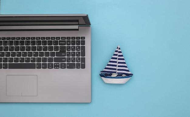 Planejamento de viagens. laptop e veleiro sobre fundo azul. vista do topo. postura plana