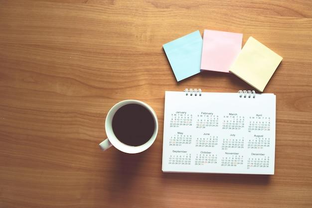 Planejamento de viagens no calendário e usar lembrete na mesa de madeira
