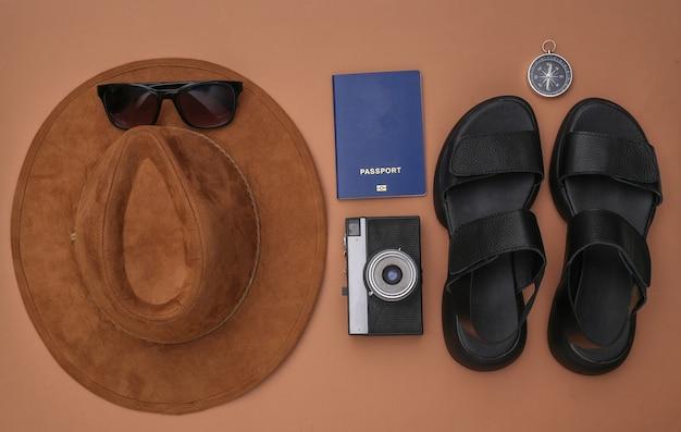 Planejamento de viagens. sandálias, chapéu e acessórios de viagem em fundo marrom. vista do topo. postura plana