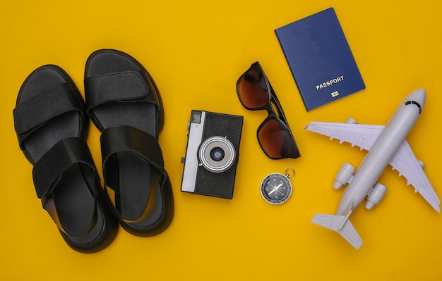 Planejamento de viagens. sandálias e acessórios de viagem em fundo amarelo. vista do topo. postura plana