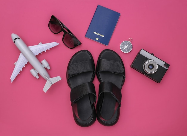 Planejamento de viagens. sandálias e acessórios de viagem em um fundo rosa. vista do topo. postura plana