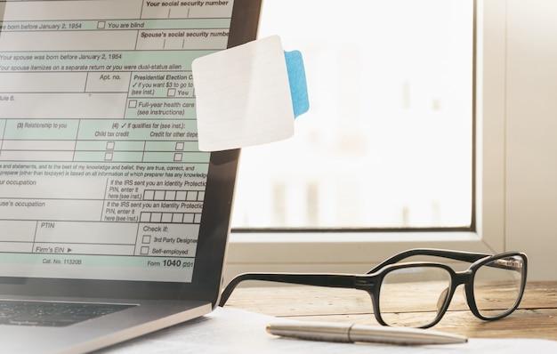 Planejamento tributário. computador portátil com formulário de imposto de renda individual com post-it em branco