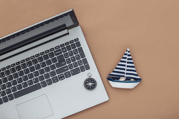 Planejamento, viagens online. laptop e veleiro, bússola em um fundo marrom. vista do topo. postura plana