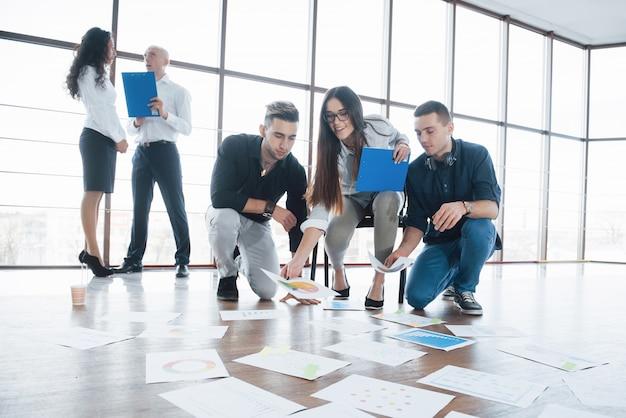 Planejando a estratégia juntos. equipe de negócios olhando papéis no chão em busca de uma idéia. realização corporativa de cooperação e conceito de trabalho em equipe