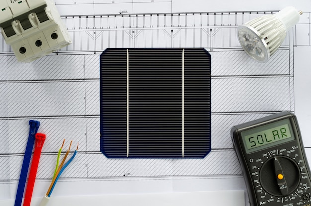Planejando a mudança para energia solar. plano de construção ou planta e células solares com mlultímetro, lâmpada led, disjuntor e cabos