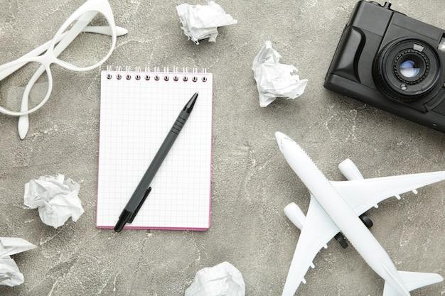 Planejando férias de verão, turismo e viagem de fundo vintage. caderno de viajantes com acessórios em cinza. postura plana.