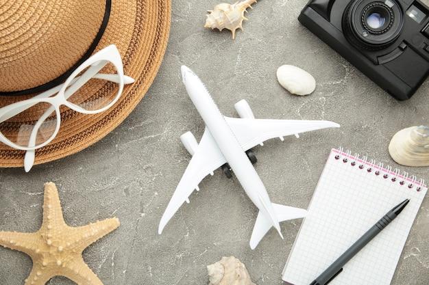 Planejando férias de verão, turismo e viagem de parede vintage. caderno de viajantes com acessórios em cinza. postura plana.