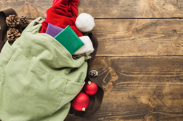 Planejando o conceito de viagens. mochila vintage com chapéu de papai noel, passaportes e decorações de natal na mesa de madeira