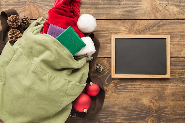 Planejando o conceito de viagens. mochila vintage com lousa em branco, chapéu de papai noel, passaportes e decorações festival de natal na mesa de madeira. .
