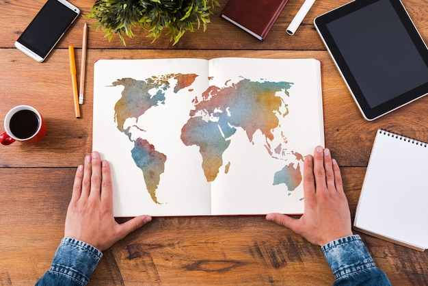 Planejando sua jornada. imagem de close-up de vista superior de um homem de mãos dadas em seu caderno com um mapa colorido enquanto está sentado na mesa de madeira