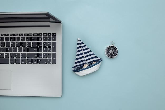 Planejando viagens. laptop e veleiro, bússola sobre fundo azul. vista do topo. postura plana